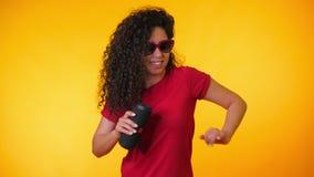 听到音乐的现代时髦女孩由无线便携式的报告人 有卷曲发型享用的年轻美女 股票视频