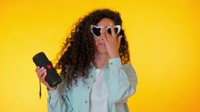 听到音乐的现代时髦女孩由无线便携式的报告人 有卷曲发型享用的年轻美女 影视素材