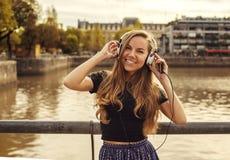 听到音乐的美丽的女孩在河附近 免版税库存照片