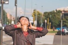 听到音乐的美丽的女孩在都市上下文 库存图片