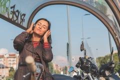 听到音乐的美丽的女孩在都市上下文 免版税图库摄影