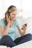 听到音乐的美丽的妇女通过耳机 免版税库存照片