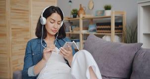听到音乐的美丽的年轻女人通过耳机使用智能手机 股票录像