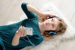 听到音乐的美丽的年轻白肤金发的妇女 库存图片