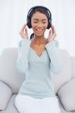 听到音乐的轻松的可爱的妇女 免版税库存图片