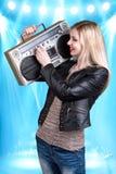 听到音乐的年轻美丽的妇女拿着一台减速火箭的录音机 免版税库存照片