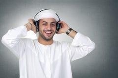 听到音乐的年轻阿拉伯人使用耳机  免版税库存照片