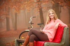 听到音乐mp3的女孩放松在秋天公园 免版税图库摄影