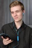 听到从您的智能手机的音乐的年轻人 免版税库存图片