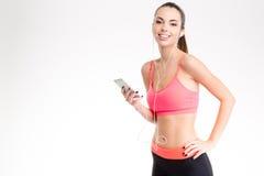 听到从手机的音乐的健身女孩使用耳机 免版税库存图片
