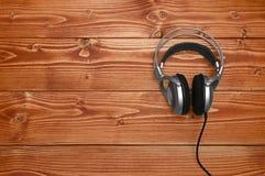 听听起来和音乐的葡萄酒耳机在木背景 图库摄影
