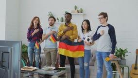 听和唱德国国歌的不同种族的小组朋友在观看前炫耀在电视的冠军 影视素材