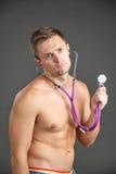 听在听诊器的年轻男性医生 免版税库存图片