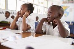 听在教训期间的两个孩子在一所小学 免版税图库摄影