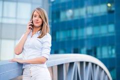 听在智能手机的电话的微笑的女商人 库存照片
