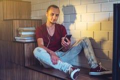 听在耳机的音频书的可爱的年轻人 技术教育的概念一种正面生活方式 库存照片