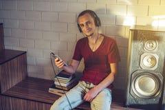 听在耳机的音频书的可爱的年轻人 技术教育的概念一种正面生活方式 免版税图库摄影