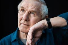听在腕子的手表的老人在黑色 免版税库存照片