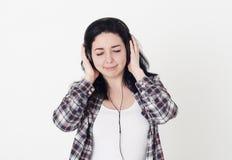 听她喜爱的歌曲的少妇或女孩结束了眼睛和拿着大耳机用手 她享用好音乐和pl 库存照片