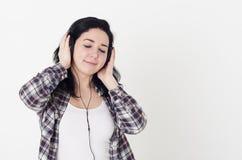 听她喜爱的歌曲的少妇或女孩结束了眼睛和拿着大耳机用手 免版税库存照片
