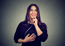 听她的与听诊器的心脏的年轻愉快的妇女 免版税图库摄影