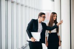 听她的同事的美丽的女实业家在关于变动全景办公室的会议上 商人指向用手 免版税库存图片