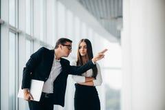 听她的同事的美丽的女实业家在关于变动全景办公室的会议上 商人指向用手 库存图片