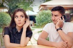 听她的男朋友的好奇女孩谈话在电话 免版税库存图片