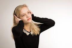 听她的耳机的少年白肤金发的女孩 免版税库存图片