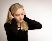 听她的耳机的少年白肤金发的女孩 免版税库存照片