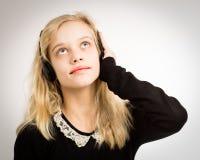 听她的耳机的少年白肤金发的女孩 免版税图库摄影