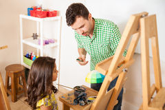 听她的艺术教师的小女孩 免版税库存图片