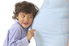 听妈妈怀孕的腹部的小男孩 免版税图库摄影