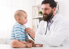 听孩子的胸口的儿科医生检查心跳 免版税库存图片