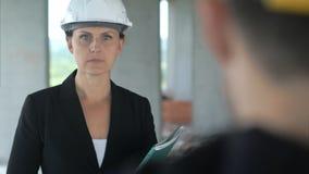 听对的妇女建筑是同事在办公楼 库存照片