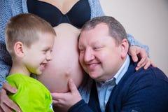 听怀孕的母亲的腹部的小男孩和爸爸 图库摄影