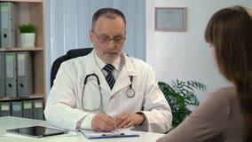 听患者和填好登记表的老练的医生 影视素材