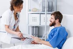 听患者的微笑的护士 免版税库存照片