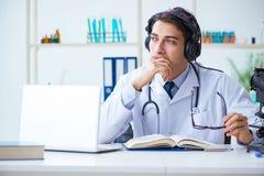 听患者的男性医生在远程医学会议期间 免版税库存图片