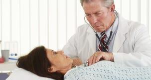听成熟患者的心脏的资深医生 免版税库存图片