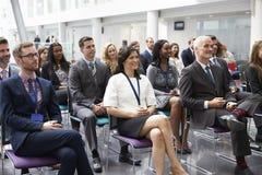 听报告人的观众在会议介绍 库存照片