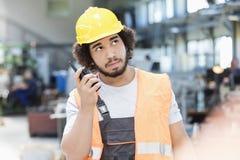 听携带无线电话的年轻体力工人,当查寻在金属工业时 免版税库存照片
