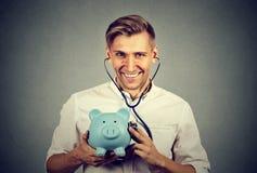 听有听诊器的存钱罐的愉快的人 免版税库存照片