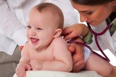 听有听诊器的小孩的后面的医生 库存图片