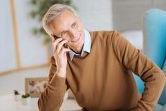 听朋友的轻松的老绅士谈话在电话 免版税库存照片