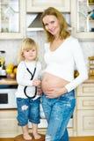 听母亲的肚子的女孩 图库摄影