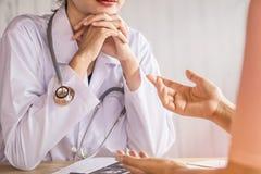 听沮丧的患者的女性医生谈论健康问题 免版税库存照片