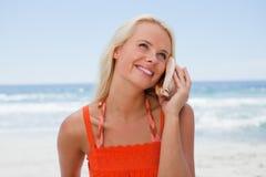 听海的声音的年轻白肤金发的妇女通过s 免版税库存图片