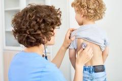 听男孩呼吸的儿科医生 图库摄影