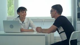 听男性患者的微笑的女性医生在她的办公室 库存图片
